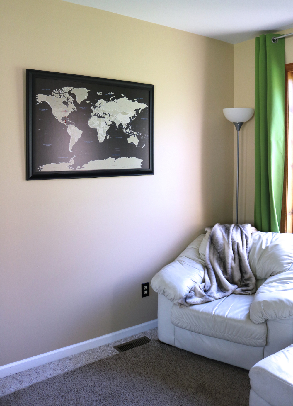 Earth tone push pin travel map framed in black hanging on sandstone living room wall.